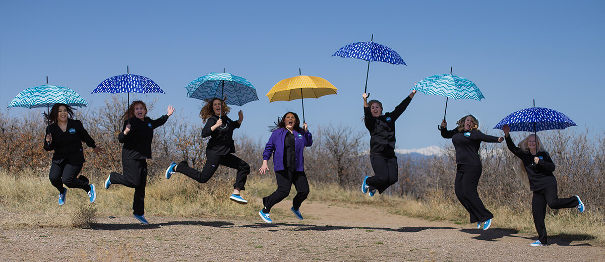 Team with umbrellas - Pediatric Dentist in Highlands Ranch, CO